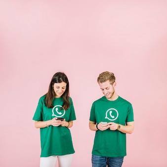 Souriant jeune homme et femme regardant téléphone portable