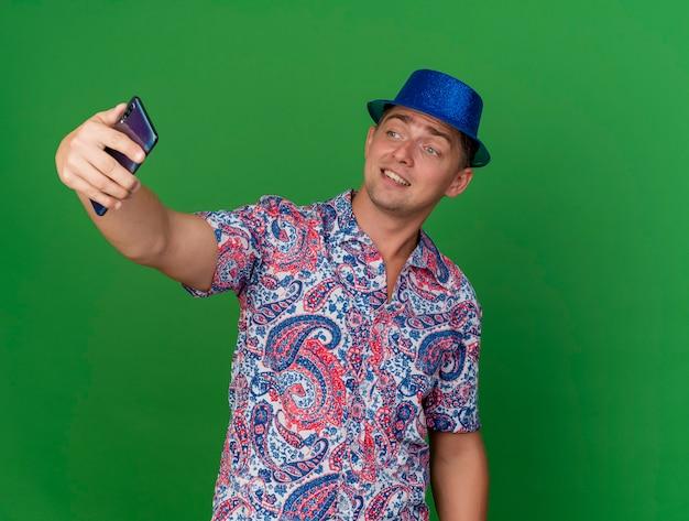 Souriant jeune homme de fête portant un chapeau bleu prendre un selfie isolé sur fond vert