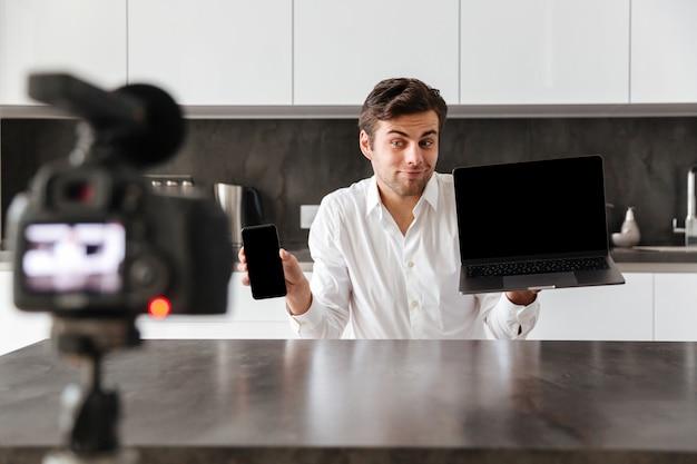 Souriant jeune homme filmant son épisode de blog vidéo