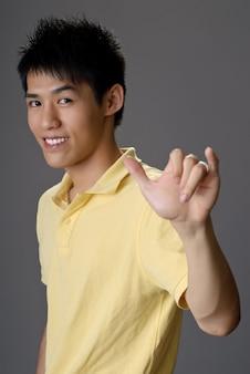 Souriant jeune homme avec un geste shaka pour saluer
