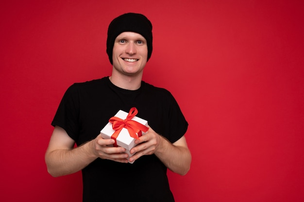 Souriant jeune homme isolé sur fond rouge mur portant un chapeau noir et un t-shirt noir tenant une boîte cadeau blanche avec ruban rouge et regardant la caméra.