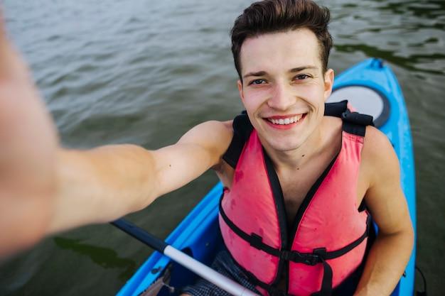 Souriant jeune homme kayakiste prenant selfie