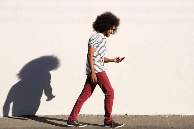 Souriant jeune homme marchant sur le trottoir avec un téléphone mobile