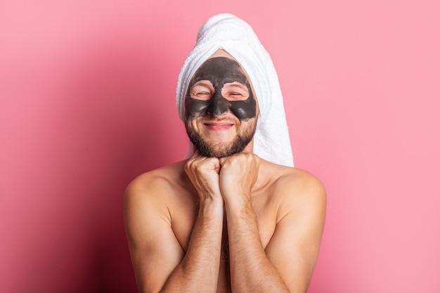 Souriant jeune homme avec masque cosmétique sur fond rose.