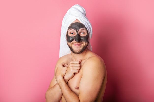 Souriant jeune homme avec masque cosmétique, nu se cachant derrière sur fond rose.