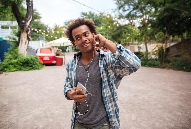 Souriant jeune homme mignon dans des écouteurs, écouter de la musique à partir d'un téléphone portable