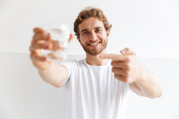 Souriant jeune homme montrant un verre d'eau, debout devant le mur à la maison