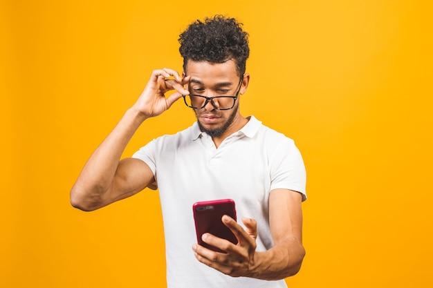 Souriant jeune homme noir dans des verres tenant le téléphone et à l'aide d'applications mobiles