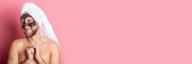 Souriant jeune homme nu avec masque cosmétique sur fond rose