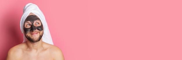 Souriant jeune homme nu avec un masque cosmétique sur son visage, regardant vers le haut sur fond rose