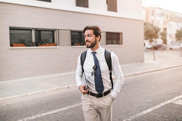 Souriant jeune homme avec un ordinateur portable marchant sur la rue