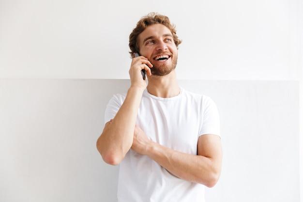 Souriant jeune homme parlant au téléphone mobile, debout devant le mur à la maison
