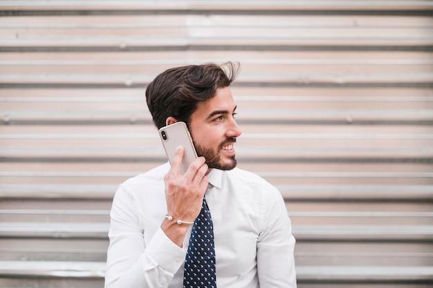 Souriant jeune homme parle sur smartphone