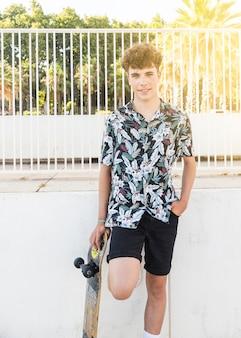 Souriant jeune homme avec planche à roulettes