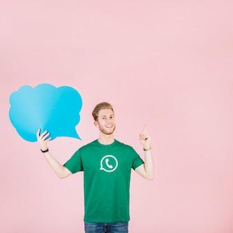 Souriant jeune homme pointant vers le haut tenant une bulle bleue vide