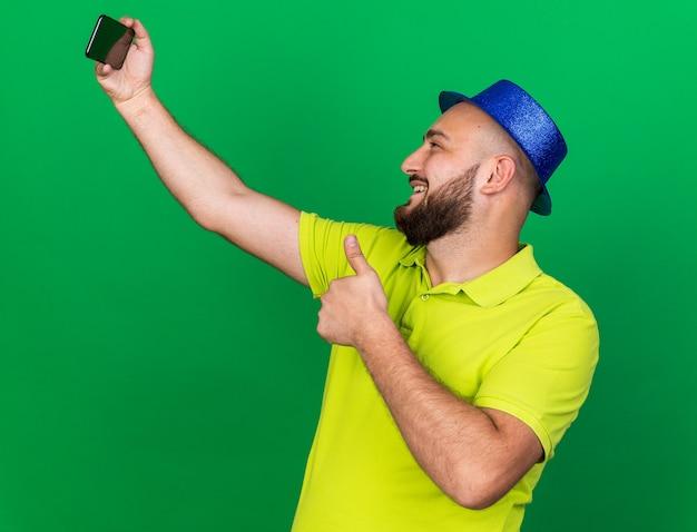 Souriant jeune homme portant un chapeau de fête bleu prendre un selfie montrant le pouce vers le haut