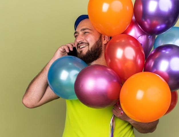 Souriant jeune homme portant un chapeau de fête tenant des ballons parle au téléphone