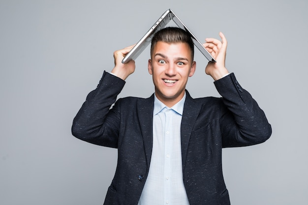 Souriant jeune homme posant avec un ordinateur portable sur la tête habillé en veste sombre en studio isolé sur mur gris