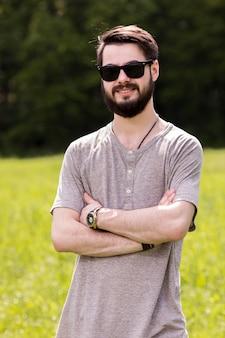Souriant jeune homme posant sur prairie avec les bras croisés