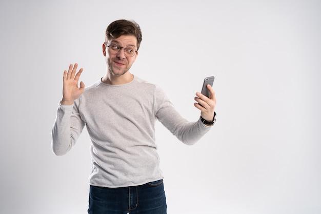 Souriant jeune homme prenant selfie par smartphone ou ayant un appel vidéo
