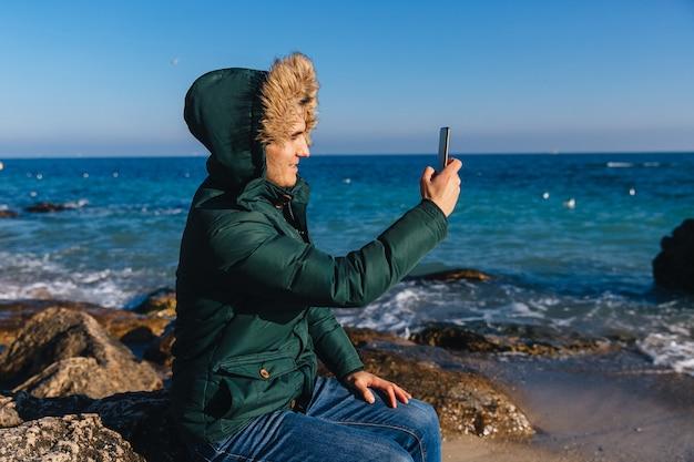 Souriant jeune homme prenant un selfie sur téléphone portable près de la mer. vêtu d'une veste chaude avec de la fourrure