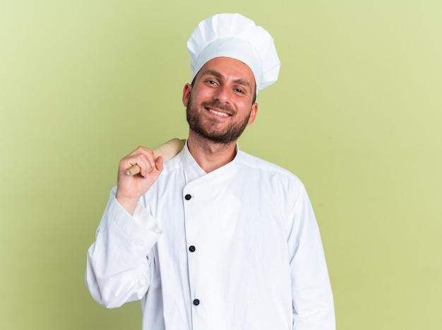 Souriant jeune homme de race blanche cuisinier en uniforme de chef et casquette tenant un rouleau à pâtisserie sur l'épaule