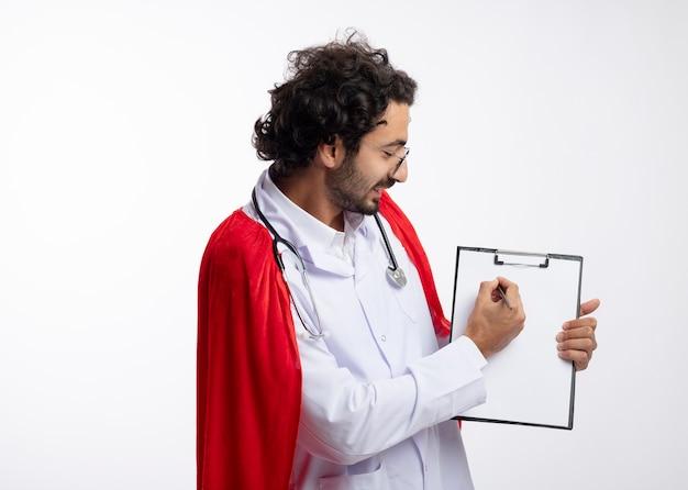 Souriant jeune homme de race blanche à lunettes optiques portant l'uniforme de médecin avec manteau rouge et avec stéthoscope autour du cou regarde et écrit sur le presse-papiers avec un crayon avec espace de copie