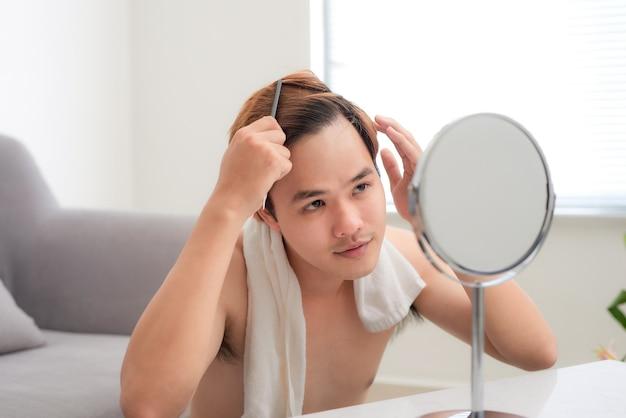 Souriant jeune homme se brosser les cheveux avec un peigne
