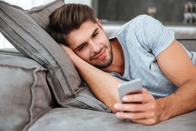 Souriant jeune homme se trouve sur le canapé et regarde au téléphone.