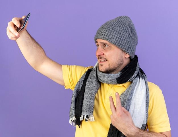 Souriant jeune homme slave malade blonde portant un chapeau d'hiver