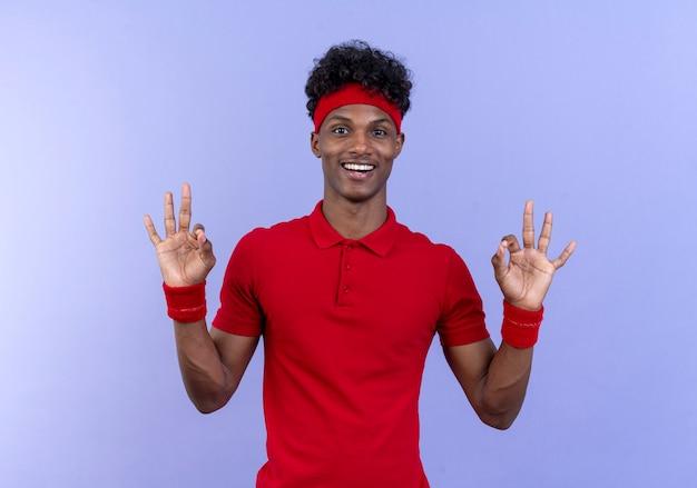 Souriant jeune homme sportif afro-américain portant bandeau et bracelet montrant le geste okey isolé sur bleu