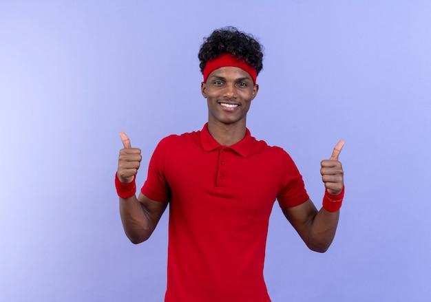 Souriant jeune homme sportif afro-américain portant bandeau et bracelet son pouce vers le haut isolé sur bleu