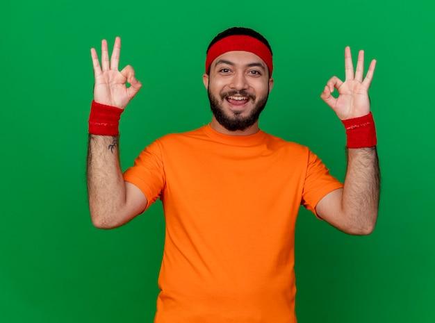 Souriant jeune homme sportif portant bandeau et bracelet montrant le geste correct isolé sur fond vert