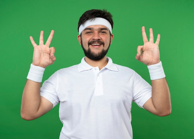 Souriant jeune homme sportif portant bandeau et bracelet montrant le geste de méditation isolé sur vert