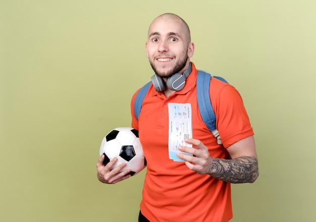 Souriant jeune homme sportif portant un sac à dos et des écouteurs sur le cou tenant la balle avec des billets isolés sur un mur vert olive avec espace copie