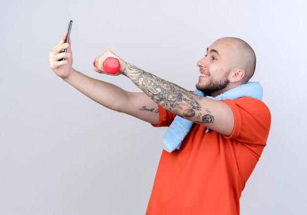 Souriant jeune homme sportif tenant des haltères et prendre un selfie isolé sur blanc