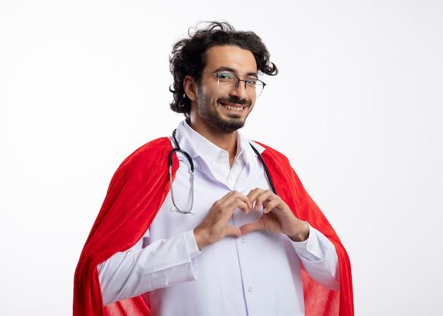 Souriant jeune homme de super-héros caucasien dans des lunettes optiques portant un uniforme de médecin avec une cape rouge et avec un stéthoscope autour du cou gestes coeur signe de la main