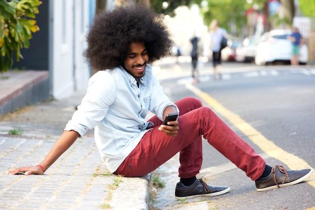 Souriant jeune homme avec un téléphone portable assis sur le trottoir