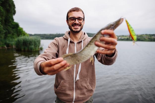 Souriant jeune homme tenant des poissons d'eau douce avec leurre