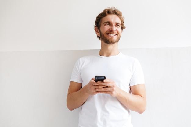 Souriant jeune homme tenant un téléphone portable, debout devant le mur à la maison