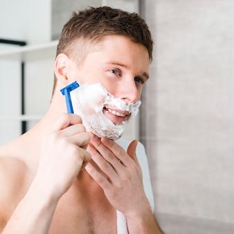Souriant jeune homme torse nu se rasant avec le rasoir bleu
