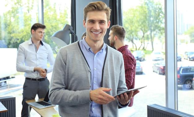 Souriant jeune homme utilisant une tablette numérique au bureau.