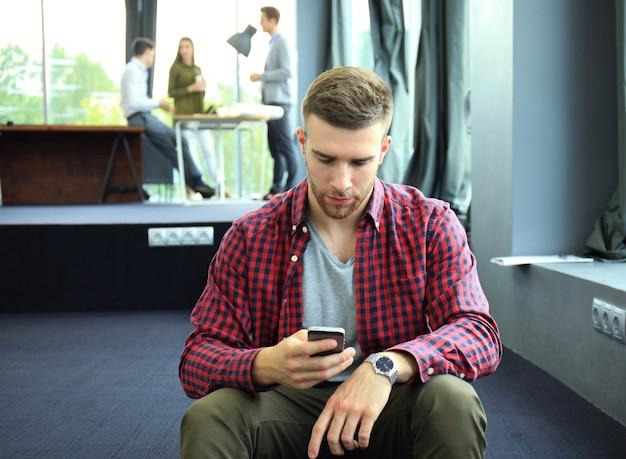 Souriant jeune homme utilisant un téléphone intelligent au bureau.