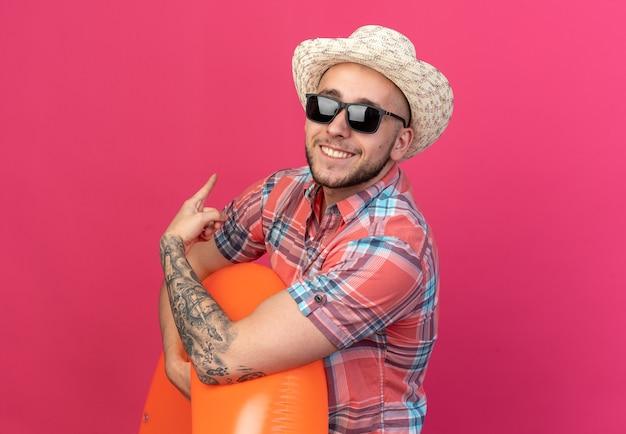 Souriant jeune homme voyageur caucasien avec chapeau de plage de paille dans des lunettes de soleil tenant un anneau de bain et pointant vers l'arrière isolé sur un mur rose avec espace de copie