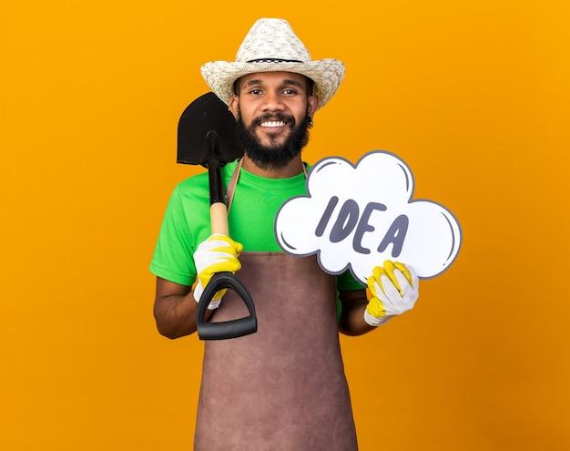Souriant jeune jardinier afro-américain portant un chapeau de jardinage et des gants tenant une pelle avec une bulle d'idée