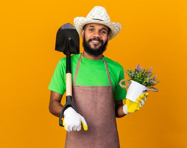 Souriant jeune jardinier afro-américain portant un chapeau de jardinage et des gants tenant une pelle avec une fleur dans un pot de fleurs