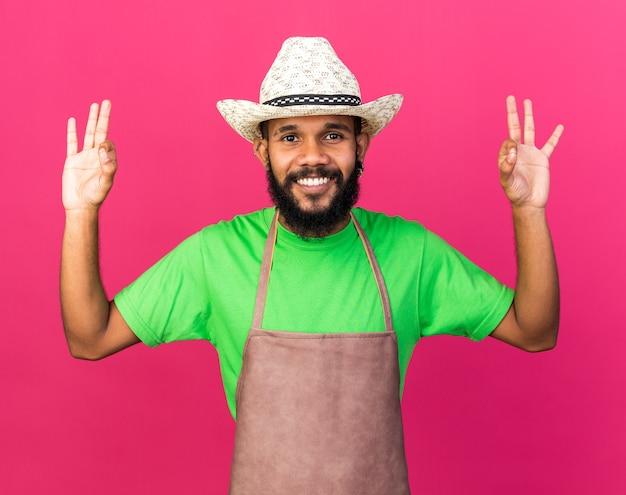 Souriant jeune jardinier afro-américain portant un chapeau de jardinage montrant un geste correct