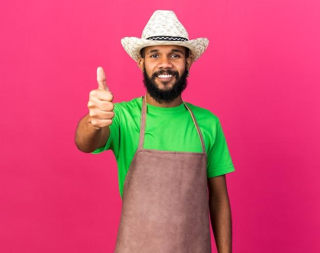 Souriant jeune jardinier afro-américain portant un chapeau de jardinage montrant le pouce vers le haut isolé sur un mur rose