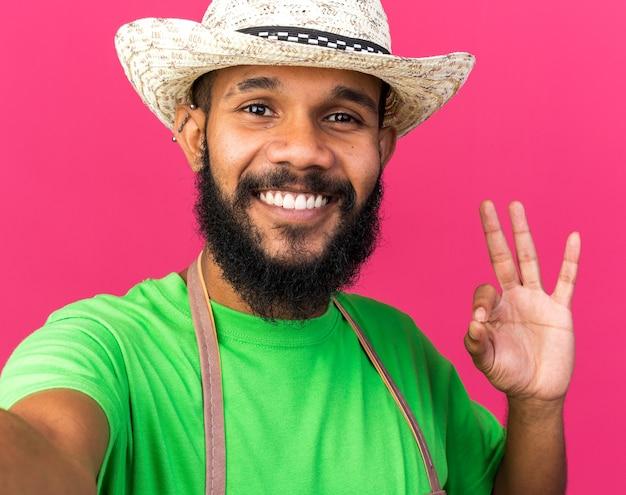Souriant jeune jardinier afro-américain portant un chapeau de jardinage tenant une caméra montrant un geste correct