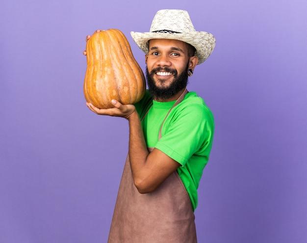 Souriant jeune jardinier afro-américain portant un chapeau de jardinage tenant une citrouille isolée sur un mur bleu